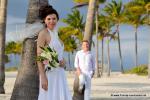Miami Wedding auf Key Biscayne am Strand mit hunderten Palmen Braut lehnt an Palme und Braeutigam schaut im Hintergrund zu