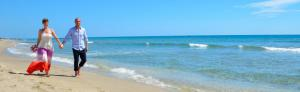 Paar laeuft am langgestreckten Sandstrand von Delray Beach entlang am blauen Meer