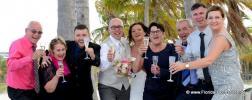 Froehliche Hochzeitsgaeste mit Bride and Groom unter Palmen