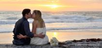 Hochzeitspaar beim romantischen Sonnenaufgang kuessend