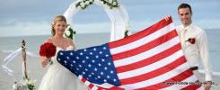Amerikanische Flagge wird von Brautpaar gehalten am Strand mit Rosenbogen in weiss geschmueckt mit Meer im Hintergrund