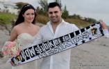 Braut und Braeutigam mit Banner und Brautstrauss am Strand von Delray Beach in Florida