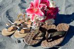 Flip Flops und Lilienstrauss in Pink im Sand