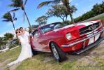 Ford Mustang in Rot mit Hochzeitspaar unter Palmen