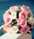 Bouquet of red and white roses flowers on the yacht with blue sea defocused background